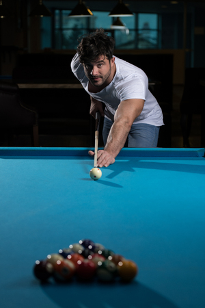 Young Man Lining To Hit Ball On Pool Table Фото со стока