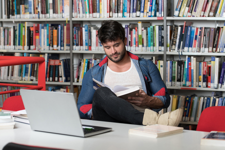 Student Preparing Exam and Learning Lessons in School Library - Making Research on Laptop and Browse Internet In the Library
