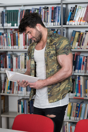 Handsome Muscular Man With Dark Hair Standing in the Library - Bodybuilder Preparing Exam and Learning Lessons in School Library Stock Photo