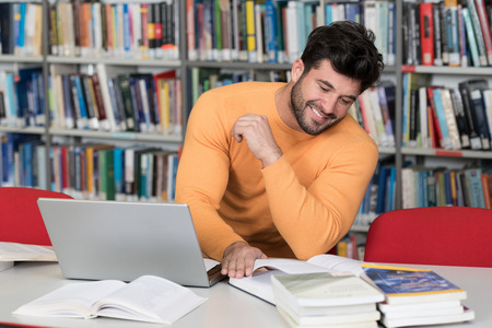 Handsome Man With Dark Hair Sitting at a Desk in the Library - Laptop and Organiser on the Table - Looking at the Screen a Concept of Studying - Blurred Books at the Back Stock Photo