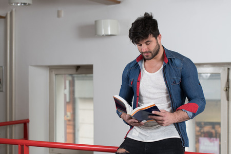 Handsome Male Student With Books Working in a High School Library