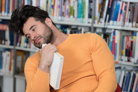 Stressed Young Male Student Reading Textbook While Sitting in Library Stock Photo