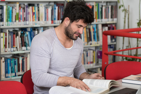 Handsome Male Student With Laptop and Books Working in a High School Library