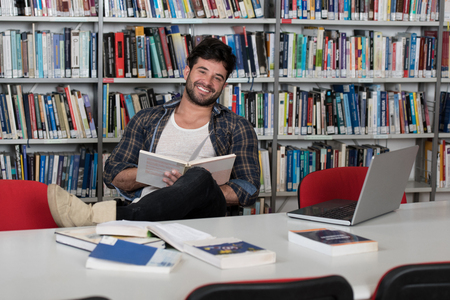 In the Library - Handsome Male Student With Laptop and Books Working in a High School - University Library - Shallow Depth of Field Stock Photo