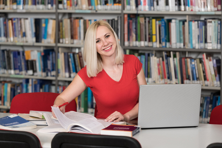 Pretty Woman With Blonde Hair Sitting at a Desk in the Library - Laptop and Organiser on the Table - Looking at the Screen a Concept of Studying - Blurred Books at the Back