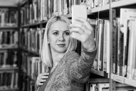 Portrait of a Happy Blonde Woman in Library at the University and Taking Selfies With Mobile Phone Stock Photo