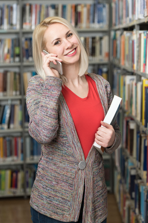 Young Beautiful Student Talking Phone While Preparing for Exams in Univercity Library