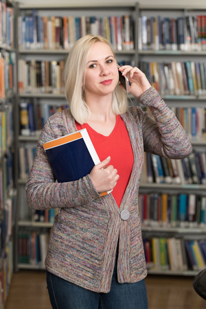 Portrait of a Happy Beautiful Woman Talking on Mobile Phone in Library at the University Stock Photo