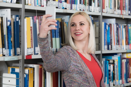 Beautiful Blonde Female College Student in Library and Taking Selfies With Mobile Phone