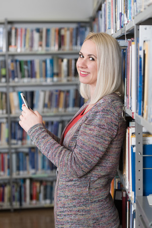 Portrait of a Happy Pretty Woman Typing on Mobile Phone in Library at the University