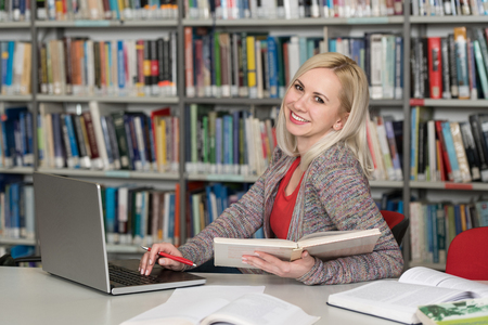 In the Library - Pretty Female Student With Books Working in a High School - University Library - Shallow Depth of Field