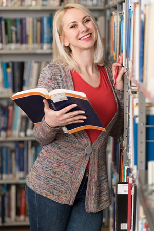 Pretty Woman With Blonde Hair Standing in the Library - Blurred Books at the Back