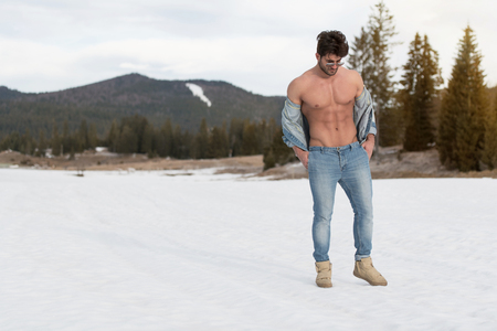 Portrait of a Young Physically Fit Man Showing His Well Trained Body While Wearing Blue Jeans - Muscular Athletic Bodybuilder Fitness Model Posing Outdoors - a Place for Your Text Stok Fotoğraf