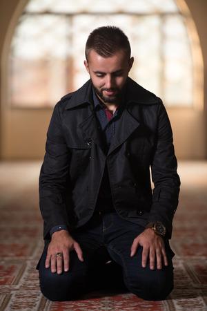 Young Muslim Man Making Traditional Prayer To God Allah