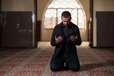 Young Muslim Man Making Traditional Prayer To God Allah