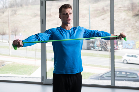 Attractive Man Exercising With A Resistance Band In Gym As Part Of Fitness Bodybuilding Training