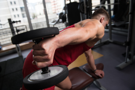 Muscular Young Man Doing Heavy Weight Exercise For Triceps With Dumbbells In Modern Fitness Center Gym Stock Photo