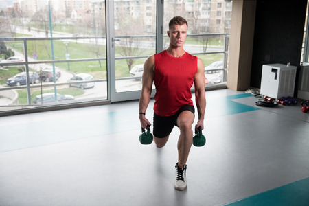 Young Man Exercising With Kettle Bell And Flexing Muscles - Muscular Athletic Bodybuilder Fitness Model Exercises