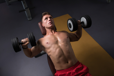 Strong Man In The Gym And Exercising Chest With Dumbbells - Muscular Athletic Bodybuilder Fitness Model Exercise