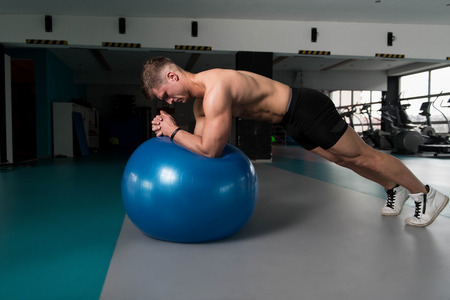 Young Man Athlete Doing Abs Exercise On Ball As Part Of Bodybuilding Training