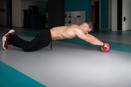 Young Man Exercising Fitness Workout For Abdominal With Toning Wheel