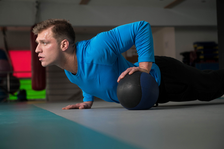 Handsome Young Man Doing Pushups With Medicine Ball As Part Of Bodybuilding Training