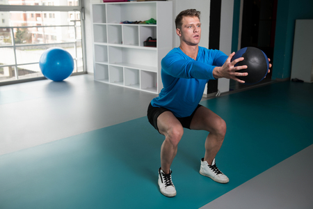 Handsome Young Man Doing Squad With Medicine Ball As Part Of Bodybuilding Training Stock Photo