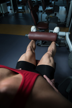 Leg Exercises Close Up -  Man Doing Leg With Machine In Gym