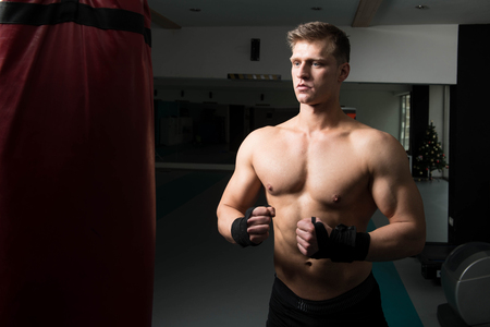 Young Man Boxing On Bag - Boxing In A Gym - The Concept Of A Healthy Lifestyle - The Idea For The Film About Boxing