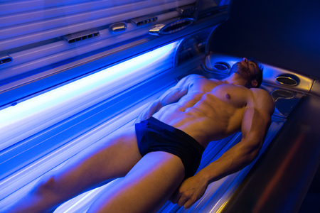 Young Muscular Man At Solarium In Beauty Salon