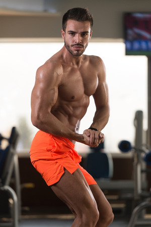 Young Man Standing Strong In The Gym And Flexing Muscles - Muscular Athletic Bodybuilder Fitness Model Posing After Exercises Standard-Bild