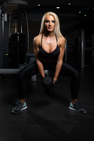 Fitness Woman Working Out Legs With Dumbbell In Fitness Center