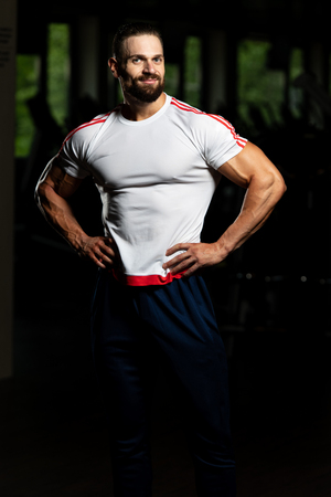 Portrait Of Personal Trainer In Sports Outfit In Fitness Center Gym Standing Strong
