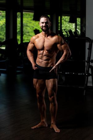 Young Man Standing Strong In The Gym And Flexing Muscles - Muscular Athletic Bodybuilder Fitness Model Posing After Exercises 版權商用圖片