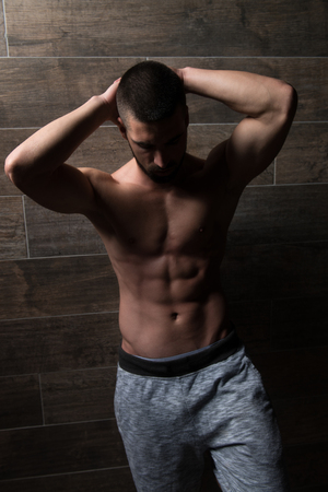 Healthy Young Man Standing Strong Standing Against a Wall and Flexing Muscles - Muscular Athletic Bodybuilder Fitness Model Posing After Exercises - a Place for Your Text Imagens