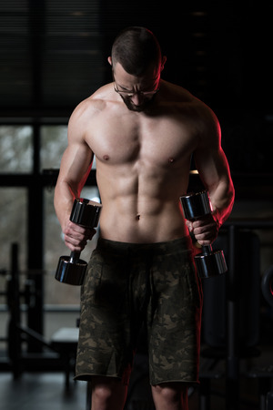Handsome Man Wearing Glasses Working Out Biceps In A Dark Gym - Dumbbell Concentration Curls
