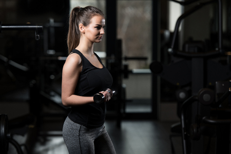 Young Fitness Woman Working Out Biceps In Fitness Center - Dumbbell Concentration Curls