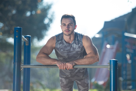 Young Man Doing Crossfit Exercise With Dips Bar in City Park Area - Training and Exercising for Endurance - Healthy Lifestyle Concept Outdoor Stockfoto