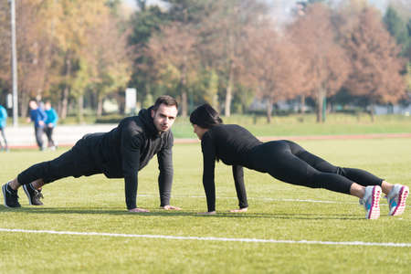 Attractive Couple Doing Push Up in City Park Area - Training and Exercising for Endurance - Fitness Healthy Lifestyle Concept Outdoor