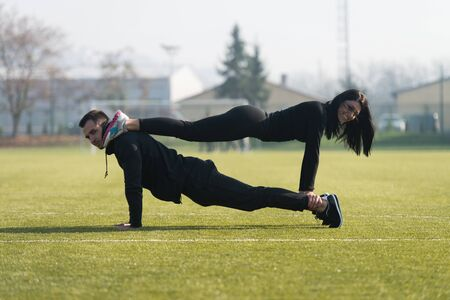 Young Couple Doing Pushups in City Park Area - Training and Exercising for Endurance - Fitness Healthy Lifestyle Concept Outdoor