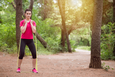 Young Woman Exercise with Resistance Band in Wooded Forest Area - Fitness Healthy Lifestyle Concept Stok Fotoğraf
