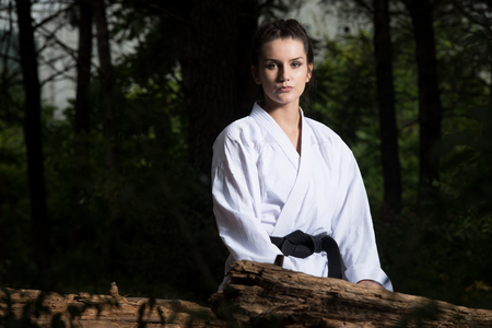 Woman Dressed In Traditional Kimono Resting After Practicing Her Karate Moves In Wooded Forest Area Stock Photo