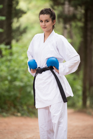 Young Woman Practicing Her Karate Moves in Wooded Forest Area - White Kimono - Black Belt
