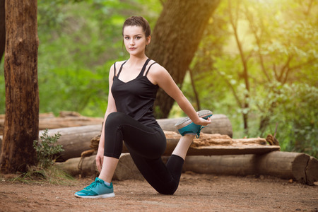 Young Woman Stretching Before Running In Wooded Forest Area - Training And Exercising For Trail Run Marathon Endurance - Fitness Healthy Lifestyle Concept