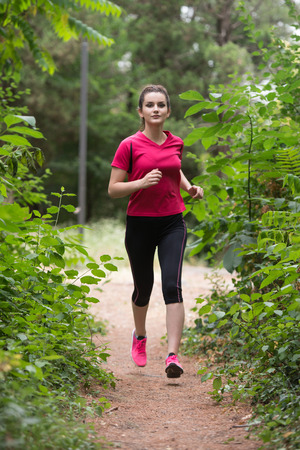 Young Woman Running In Wooded Forest Area - Training And Exercising For Trail Run Marathon Endurance - Fitness Healthy Lifestyle Concept Stock Photo