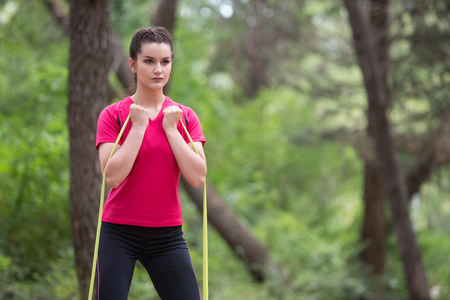 Young Woman Exercise with Resistance Band in Wooded Forest Area - Fitness Healthy Lifestyle Concept Stock Photo