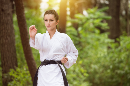 Young Woman Dressed In Traditional Kimono Practicing Her Karate Moves in Wooded Forest Area - Black Belt