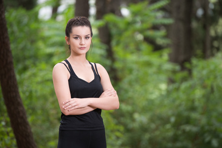 Portrait of a Young Woman Running In Wooded Forest Area - Training And Exercising For Trail Run Marathon Endurance - Fitness Healthy Lifestyle Concept