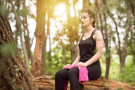 Young Woman Resting After Running In Wooded Forest Area - Training And Exercising For Trail Run Marathon Endurance - Fitness Healthy Lifestyle Concept