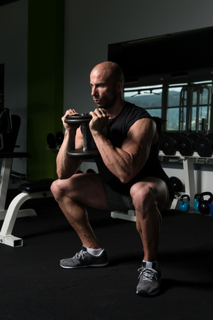 Strong Man In The Gym Exercising Hamstrings With Dumbbells - Muscular Athletic Bodybuilder Fitness Model Exercise